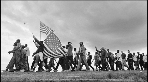 The Selma to Montgomery March for voting rights was the largest and most significant march of civil rights history. Here marchers and flags cross the horizon. In the air, a US Army reconnisance plane on the lookout for threats to the march.