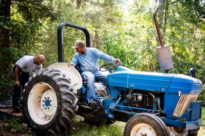 """Jock Webb ripara il trattore di Clarence Davis, foto Roger Stephenson."""