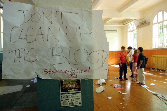 "A note reading ""Don't Clean Up The Blood"" hangs in the headquarters of the umbrella anti-globalisation protest movement, the Genoa Social Forum (GSF), 22 July 2001 after an overnight police raid in Genoa. Activists at the scene appeared shaken and horrified by the police action, calling it an unprovoked and brutal attack, as a helicopter hovering at rooftop height lit up the streets with floodlights. AFP PHOTO GERARD JULIEN"