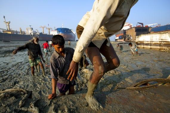 Giovani operai pakistani a contatto con fanghi nocivi