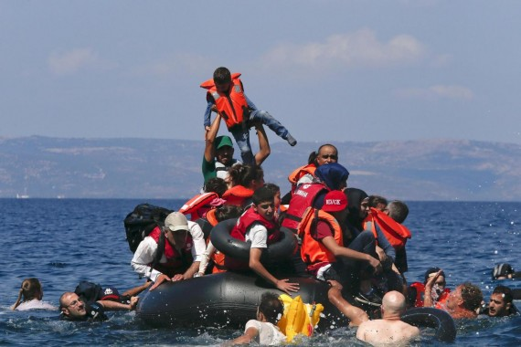 A refugee raises a child into the air as Syrian and Afghan refugees are seen on and around a dinghy that deflated some 100m away before reaching the Greek island of Lesbos, September 13, 2015. Of the record total of 432,761 refugees and migrants making the perilous journey across the Mediterranean to Europe so far this year, an estimated 309,000 people had arrived by sea in Greece, the International Organization for Migration (IMO) said on Friday. About half of those crossing the Mediterranean are Syrians fleeing civil war, according to the United Nations refugee agency. REUTERS/Alkis Konstantinidis