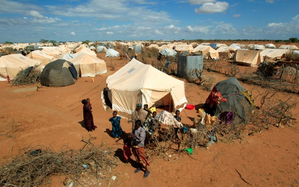 Refugees stand outside their tent at the Ifo Extension refugee camp in Dadaab, near the Kenya-Somalia border in Garissa County, Kenya